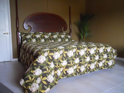 King size mahogony bed in bedroom. Has view to ocean and town