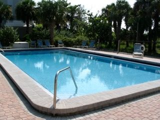 View of large heated pool with poolside loungechairs