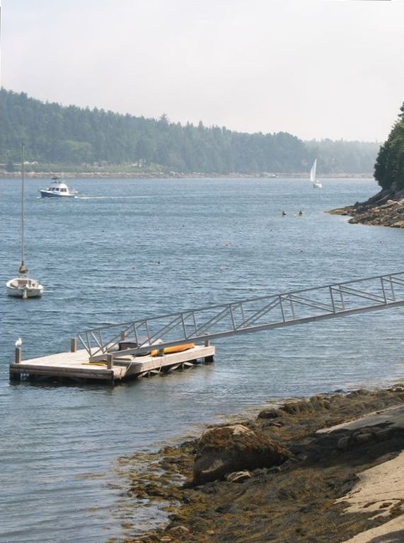 Floating dock at low tide. Mussels can be harvested from rocks at this time.