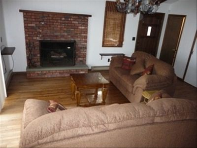 Cozy great room with cathedral ceiling, wood burning fireplace queen sofa bed