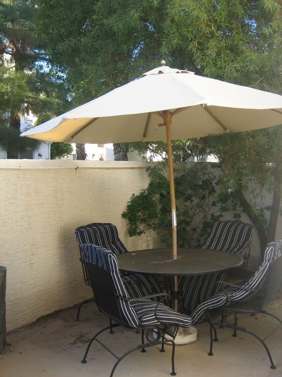 Patio with padded chairs and umbrella