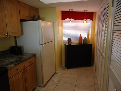 Kitchen shows the pantry door, and doors to the washer and dryer