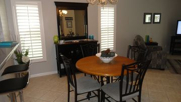 Dining area in the great room with 2 bar stools, table for 4, & sideboard.