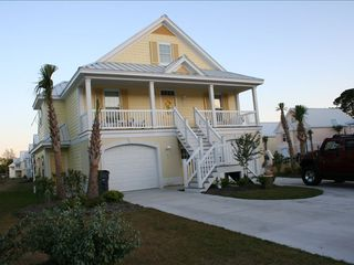 Surfside Beach house photo - Front of the home with a full porch with seating.