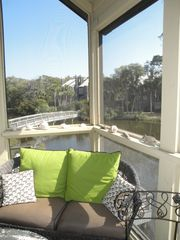 Kiawah Island villa photo - Outdoor living room on private screen porch. Footbridge to beach access beyond.
