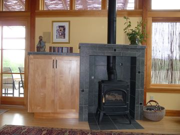 Living room warming stove with electronics/TV cabinet to left