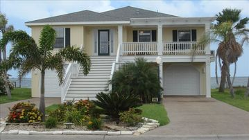 Rockport house rental - Front of the house surrounded by palm trees facing canal and backing up to bay