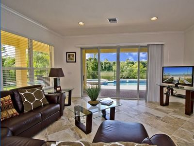 Family Room looking out to patio, heated pool/hot tub. Direct Southern exposure!