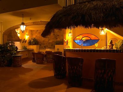 Pool Deck at night, palapa-covered bar & alcove, ideal for evening entertainment