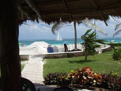 A view from under one of the front palapa's looking toward the patio and beach.