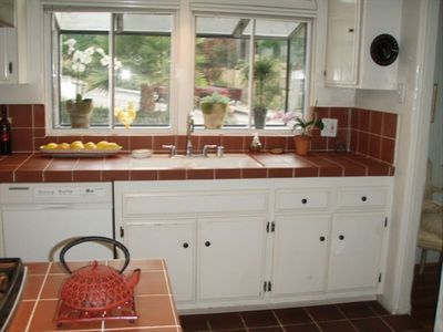 Kitchen sink with views of Spanish villa and ocean to the right. Gas stovetop.