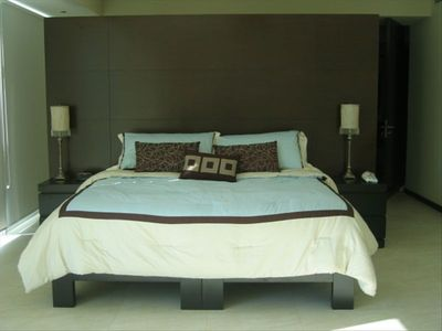 Master bedroom w/ a king size bed, 32-inch flat screen TV, and its own bathroom