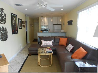 Open floor plan with plenty of light, comfortable leather couch and new art work