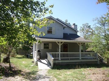 Lewis Smith Lake cottage rental - The front porch with a swing and gas grill!