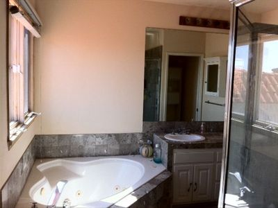view of master bath w/ dual vanity sinks, spa tub, standing shower, large window
