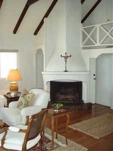 Gas fireplace with staircase behind to upper view deck.