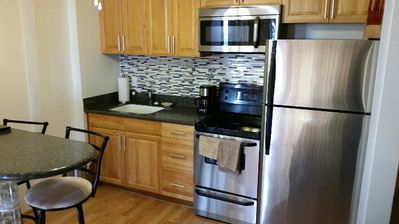 Brand new cabinets with new glass tile backsplash.