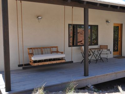 Covered porch with bistro table and swing beckoning guests to relax