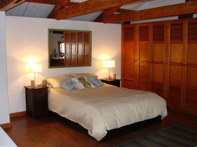 wood accents and vaulted ceilings highlight the romanitic bedroom