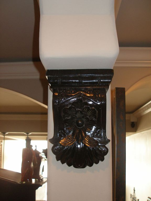 Stained wooden corbel under arches