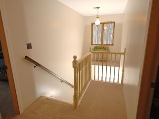 Hillman house photo - An open staircase and railing separates the upstairs from the activity downstair