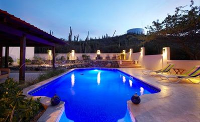 Pool with lighted backyard around sunset