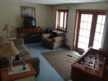 Downstairs living room with gaming system, karaoke, foosball, card table/chips