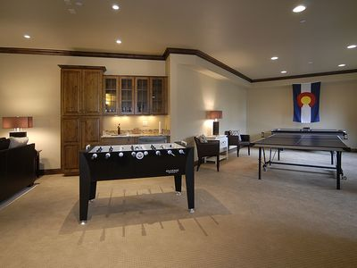 Game area with foozeball, ping-pong, air hockey table and wet bar.