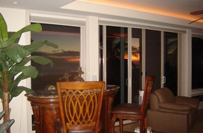 View of living room from dining area, notice the sunset thru the sliding doors