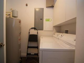 Cocoa Beach condo photo - Laundry room with heat pump/a/c, full size washer & dryer & storage cabinets.