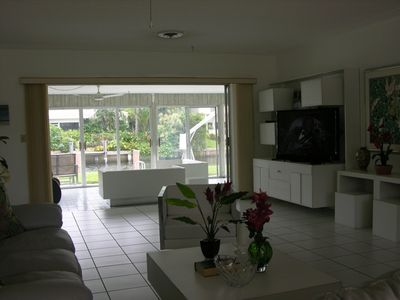 Large living room with large screen television walking out to large porch.