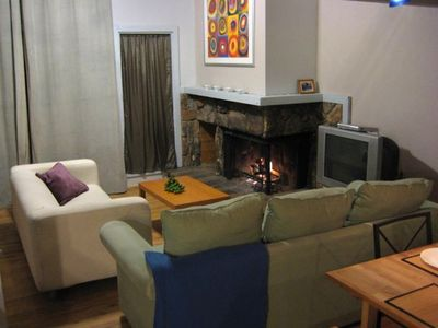Living room has vaulted ceilings, wood fireplace with gas starter and balcony.