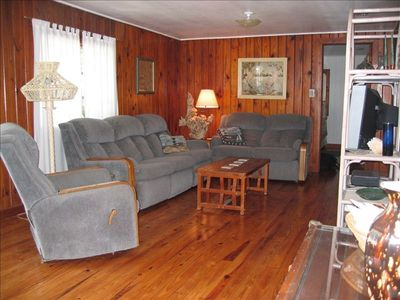 Living room area with original knotty pine floors and walls