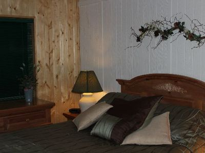 guest bedroom with queen bed, pine wall, TV, mirror closet doors