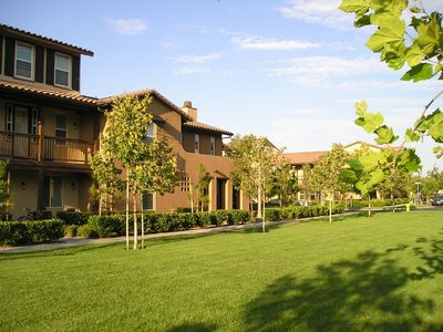 The house faces a green space of luscious manicured grass.