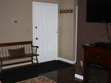 Condo entrance with bench and coat rack