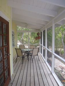 Front screened in porch - one side dining / one side muskoka chairs for relaxing
