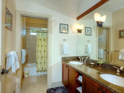 Guest bath has a granite double vanity and separate shower/bath area