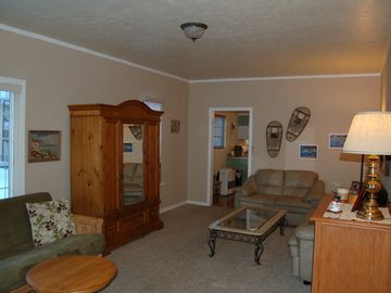 Living room has antique snowshoes, fine art, leather couches & pine armoire