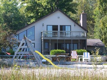 Harrisville house rental - Lakeside of house with screened in porch and balcony from master bedroom