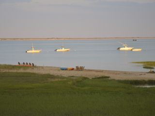 Chatham house photo - our beach with pair of chairs and kayaks-- and neighbors 5 chairs.