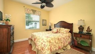 Marco Island house photo - Guest bedroom with sunny yellow duvet and Tommy Bahama furniture, flat screen tv