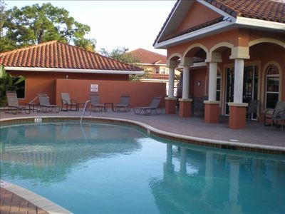 Swimming pool with plenty of lounging area & umbrella covered tables.
