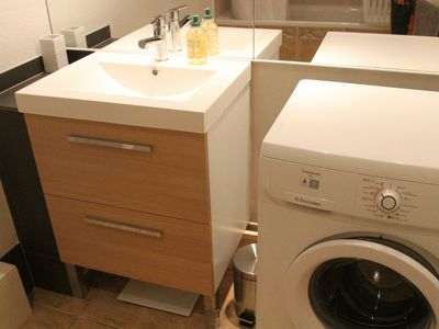The bathroom also includes a washing machine.