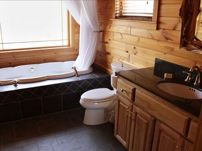Upper floor bath with jetted tub and garden views, granite and slate