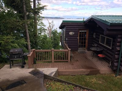 Cabin sits above lake with stair access to fire pit, sitting area & dock.