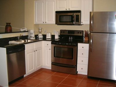 Suite features full kitchen with stainless steel appliances & cookware.