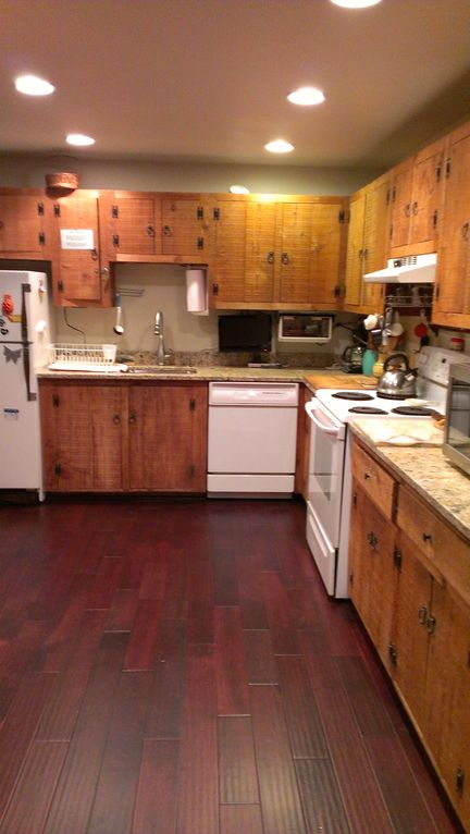 Our very well equipped kitchen now has granite counter tops and a wooden floor.