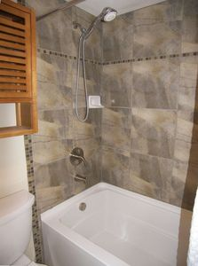 New deep soaking tub with stone and glass tile accents unit T204