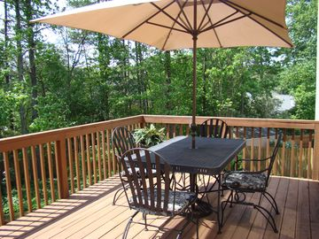 Rod iron table/umbrella with gas grill on deck overlooking private backyard.